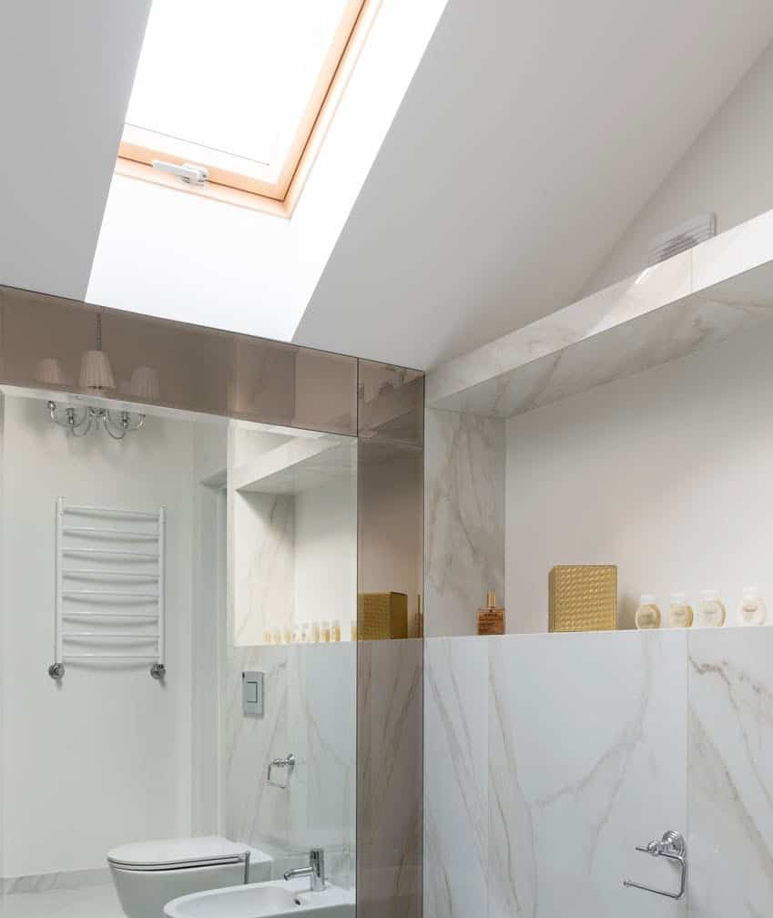 Marble bathroom brightened by skylight window