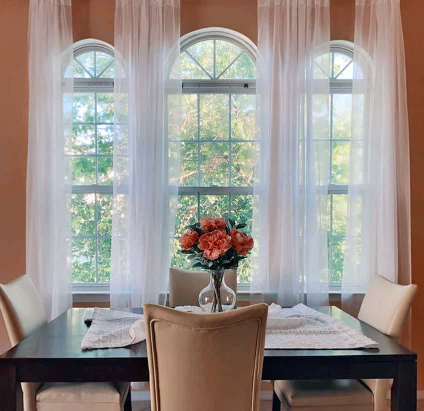 Dining table facing tall arched windows revealing trees